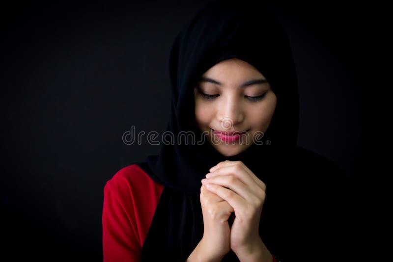 giovane donna musulmana religiosa che prega su fondo nero immagini stock