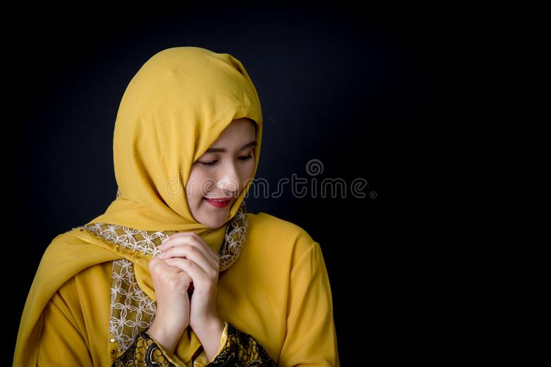 giovane donna musulmana religiosa che prega su fondo nero fotografia stock