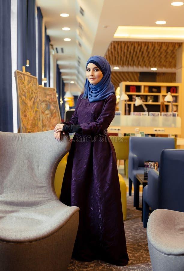 Giovane donna musulmana in un bello e vestito moderno che sta nell'ingresso immagine stock