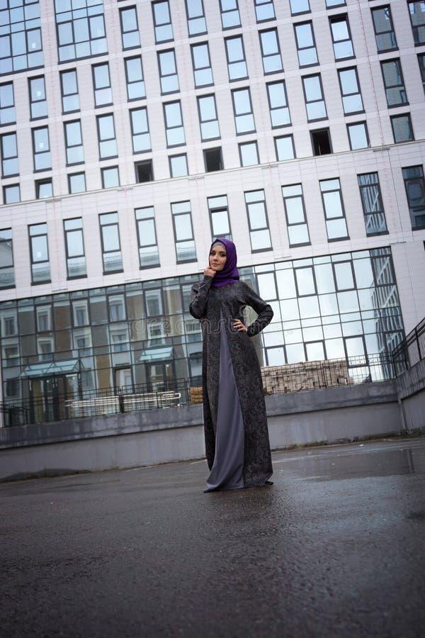 Giovane donna musulmana in vestito orientale su un fondo di una costruzione moderna immagine stock