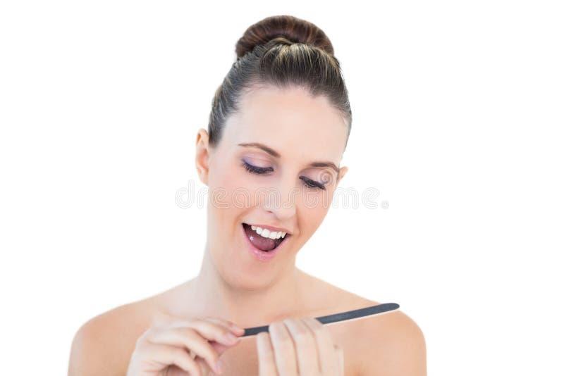 Giovane donna naturale allegra che usando l'archivio di chiodo fotografia stock