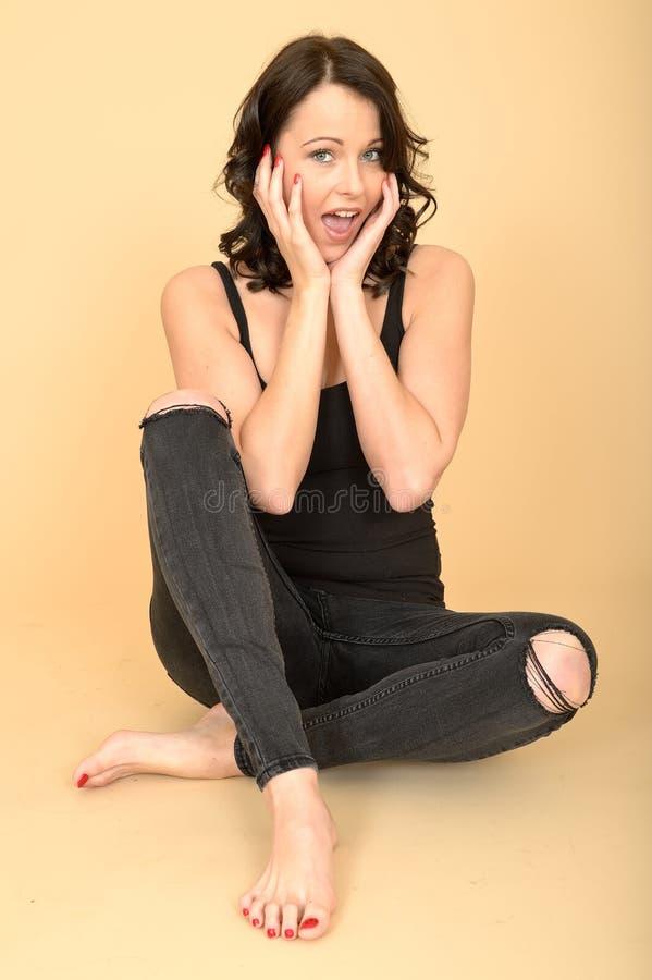 Giovane donna naturale sorpresa attraente che si siede sul pavimento fotografia stock libera da diritti