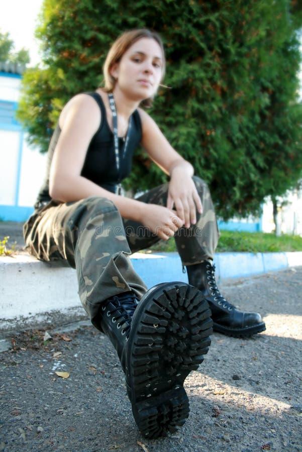 Giovane donna nei caricamenti del sistema e nel camuffamento dell'esercito immagini stock