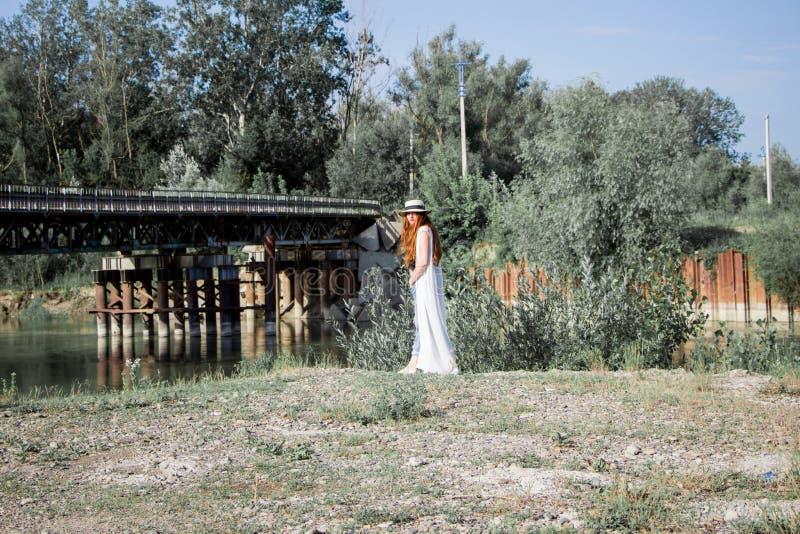 Giovane donna nel cappello che cammina nel parco fotografia stock