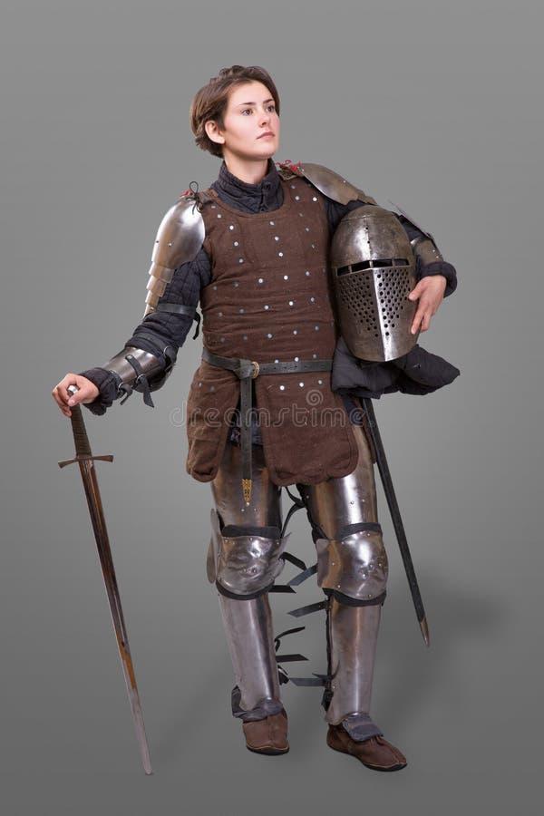 Giovane donna nel casco della tenuta di Armour del cavaliere in una mano e spada sulla sua spalla sopra fondo grigio fotografie stock