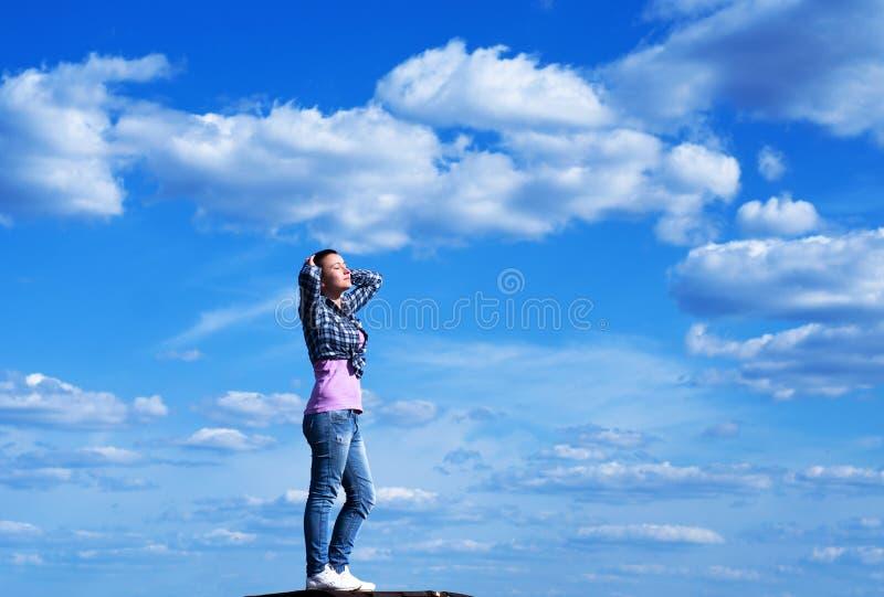 Giovane donna nel cielo blu immagine stock