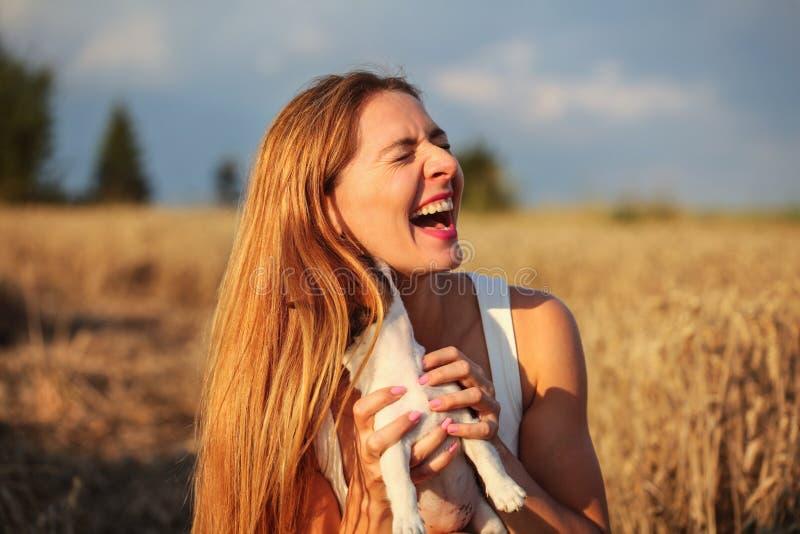Giovane donna nel giacimento di grano acceso dal sole di pomeriggio, tenente cucciolo t immagini stock