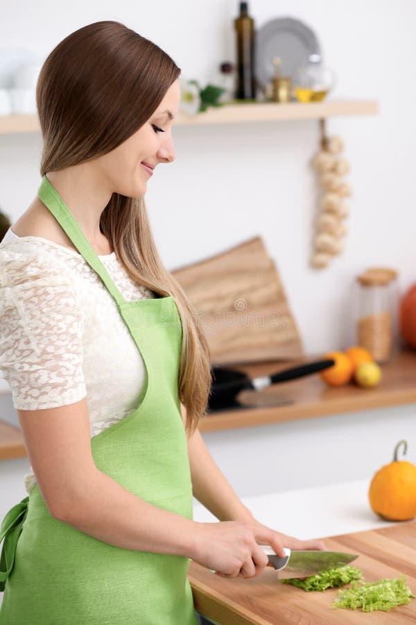 Giovane donna nel grembiule verde che cucina nella cucina Casalinga che affetta insalata fresca fotografie stock