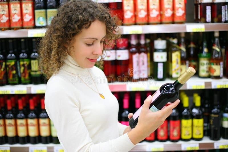 Giovane donna nel negozio di vino immagini stock libere da diritti