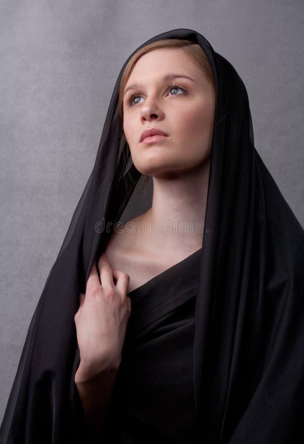 Giovane donna nel nero con la testa coperta fotografie stock