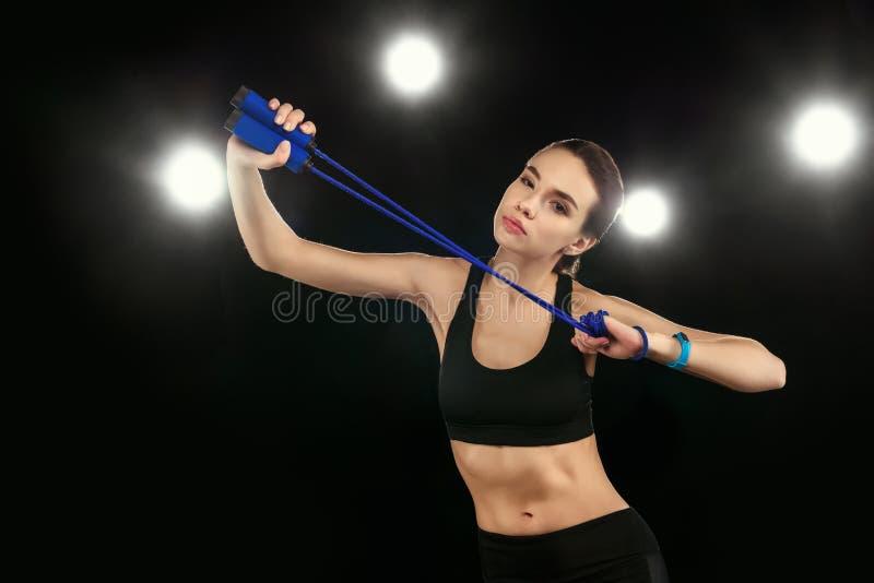 Giovane donna nel salto della corda della tenuta degli abiti sportivi ed esaminare macchina fotografica fotografie stock