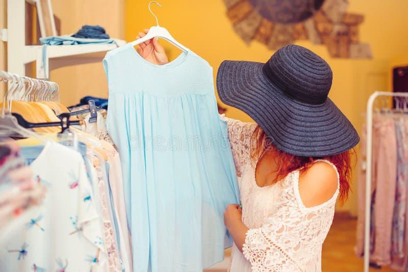 Giovane donna nell'acquisto black hat nel deposito delle donne Tempo di acquisto Vendita di estate fotografie stock
