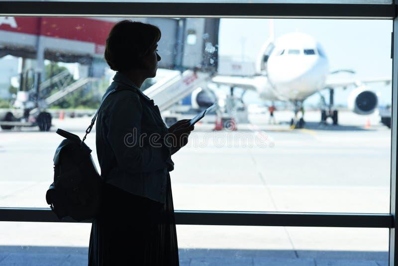 Giovane donna nell'aeroporto, osservante attraverso la finestra gli aerei fotografia stock libera da diritti