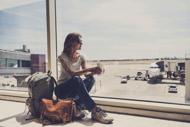 Giovane donna nell'aeroporto, osservante attraverso la finestra gli aerei e caffè bevente, viaggio, vacanze e conce attivo di sti immagine stock libera da diritti
