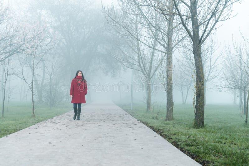 Giovane donna nella camminata rossa dal parco della città in nebbia immagine stock libera da diritti