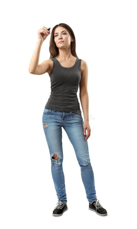 Giovane donna nella cima senza maniche grigia e blue jeans che stanno e che posano con l'indicatore a disposizione come se scrive immagini stock