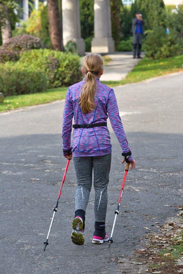 Giovane donna nella corsa di camminata nordica sulle vie della città fotografie stock libere da diritti