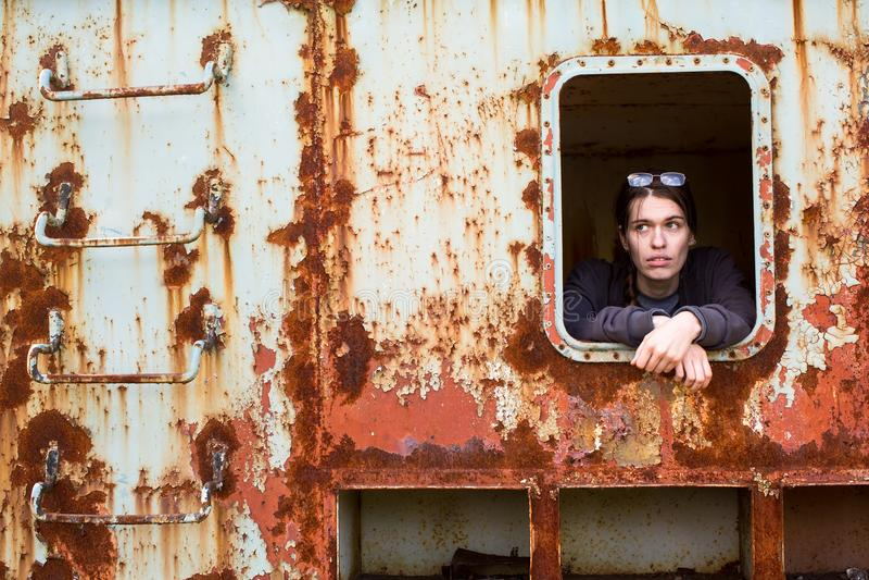 Giovane donna nella finestra di un oggetto arrugginito abbandonato del ferro fotografia stock