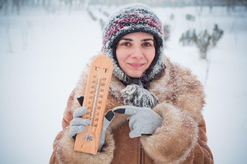 Giovane donna nella neve con un termometro immagine stock libera da diritti