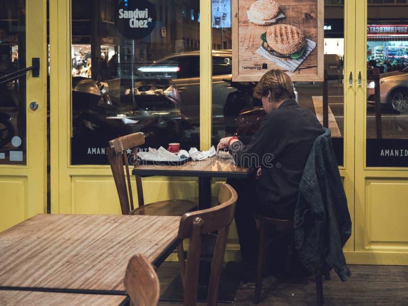 Giovane donna non-sposata che mangia dentro il caffè spagnolo fotografia stock libera da diritti