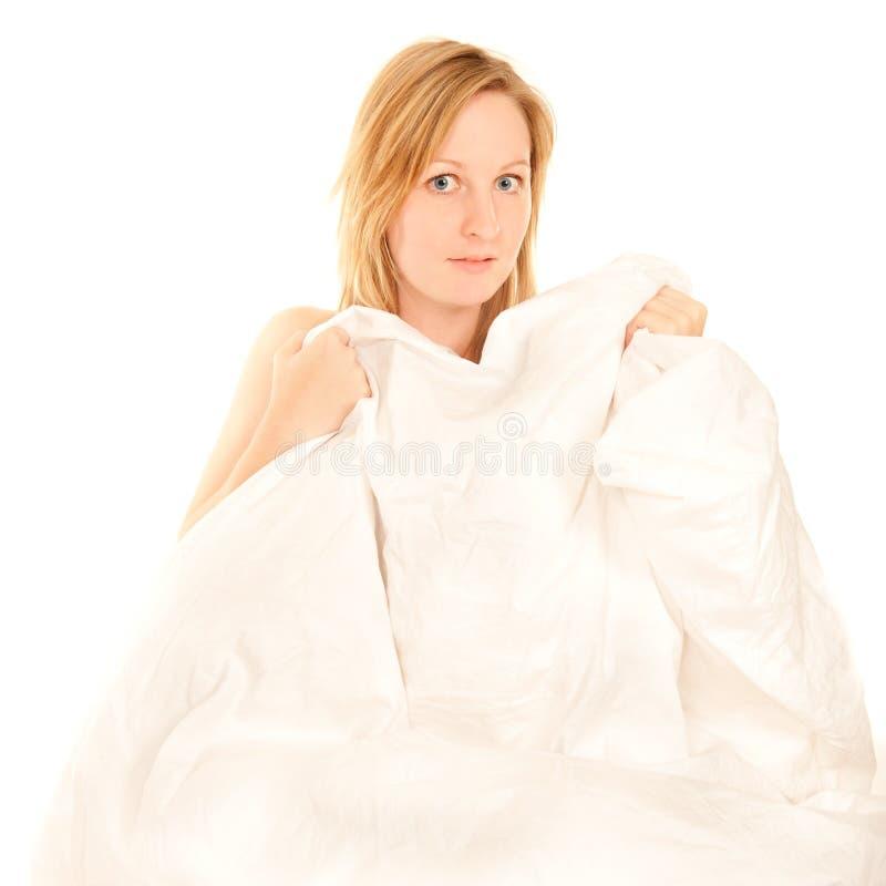 Giovane donna nuda che si nasconde dietro le coperte da letto immagini stock