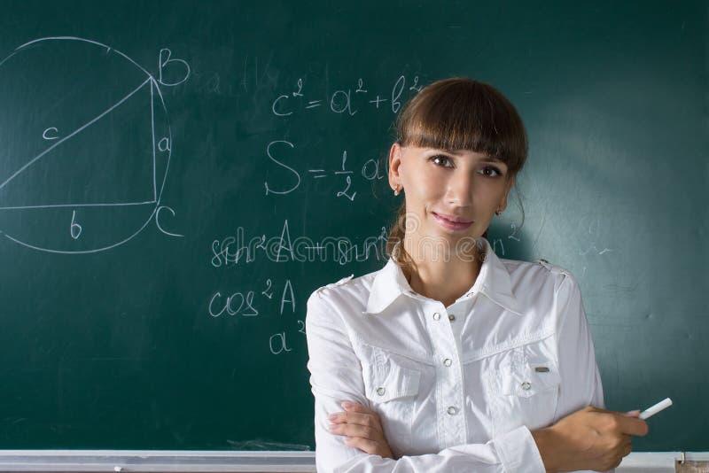 Giovane donna o studente dell'insegnante alla lavagna immagine stock libera da diritti