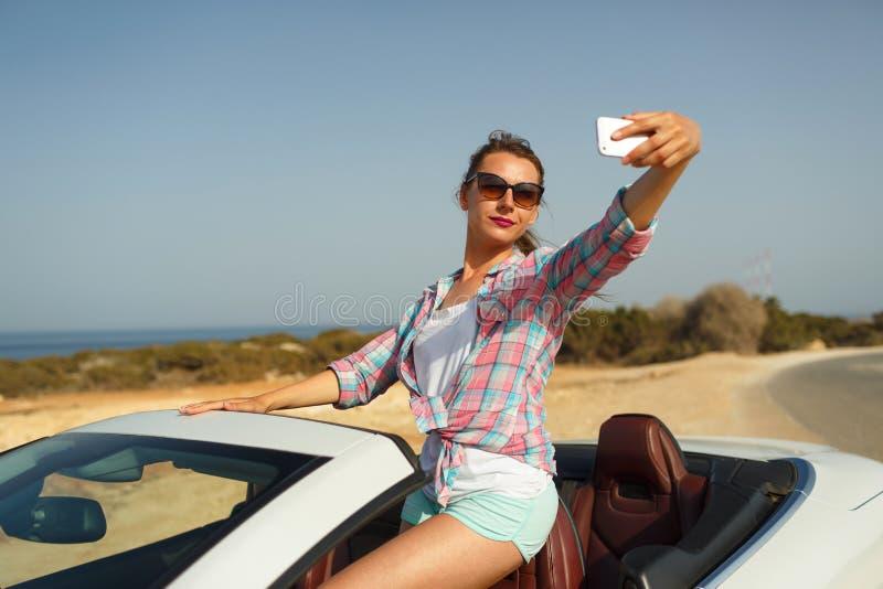 Giovane donna in occhiali da sole che fanno autoritratto che si siede nel Ca fotografie stock