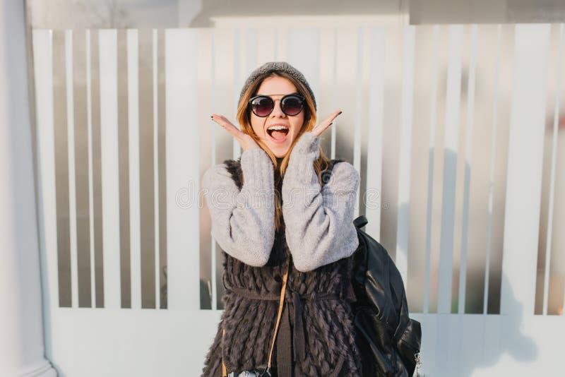 Giovane donna in occhiali da sole d'avanguardia che gode di buon tempo durante la passeggiata di mattina Ritratto all'aperto dell fotografia stock libera da diritti