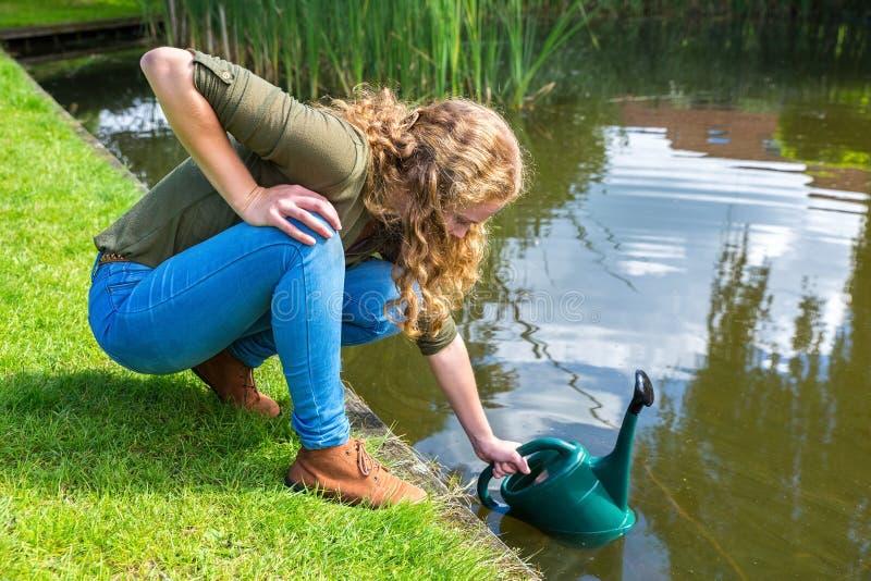 Giovane donna olandese che riempie macchina per colata continua verde di acqua fotografia stock libera da diritti