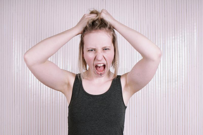 Giovane donna oltraggiata che ha un capriccio di carattere che grida e che grida fotografia stock libera da diritti