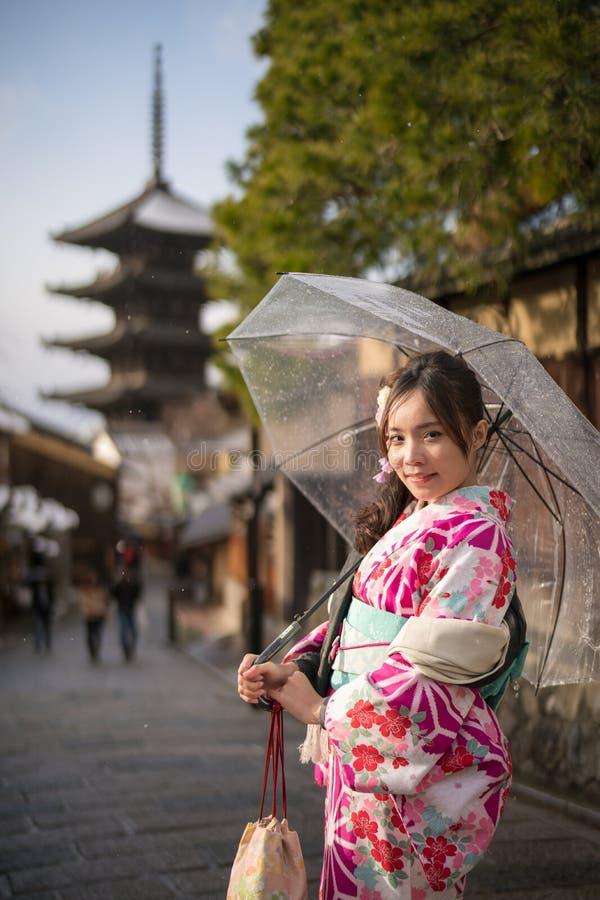 Giovane donna in ombrello della radura del kimono fotografia stock libera da diritti
