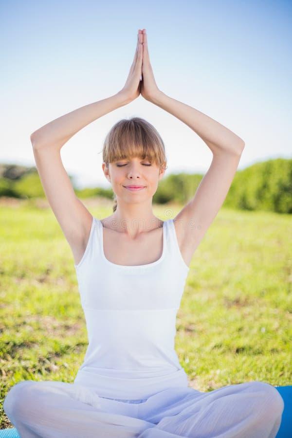 Giovane donna pacifica che si rilassa facendo yoga immagine stock