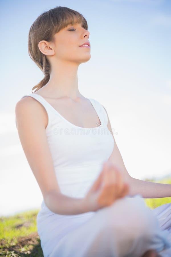 Giovane donna pacifica che si rilassa nella posizione di yoga fotografia stock libera da diritti