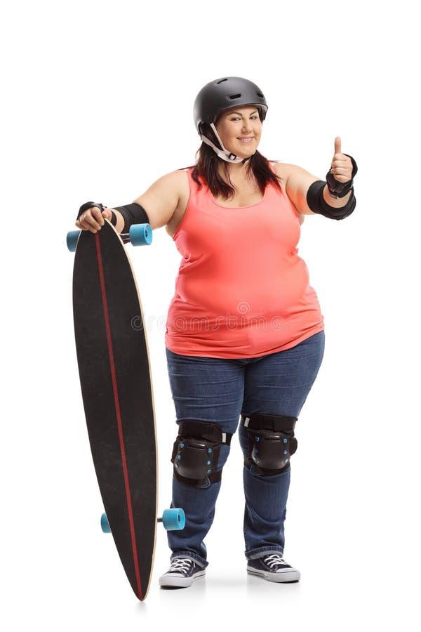 Giovane donna paffuta con l'ingranaggio protettivo e un longboard che mostra i pollici su fotografia stock