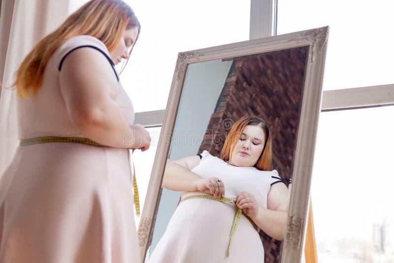 Giovane donna paffuta piacevole che misura la sua vita fotografia stock libera da diritti