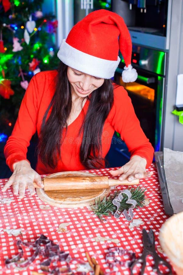 Giovane donna in pan di zenzero di cottura del cappello di Natale a fotografia stock