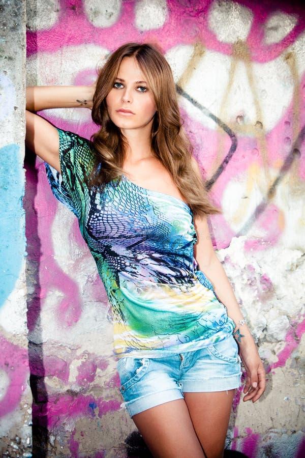 giovane donna in parete fronta dei graffiti immagine stock