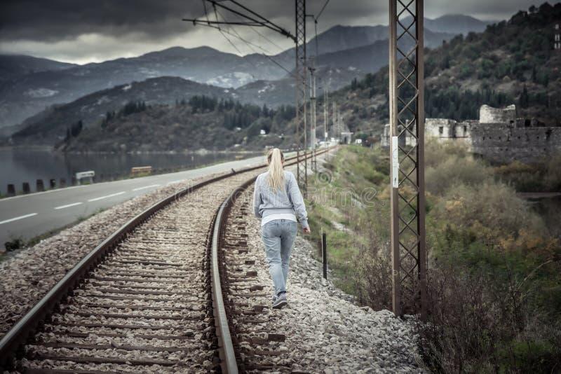 Giovane donna pensierosa che entra via in distanza attraverso il percorso ferroviario nel giorno nuvoloso con il cielo drammatico immagini stock