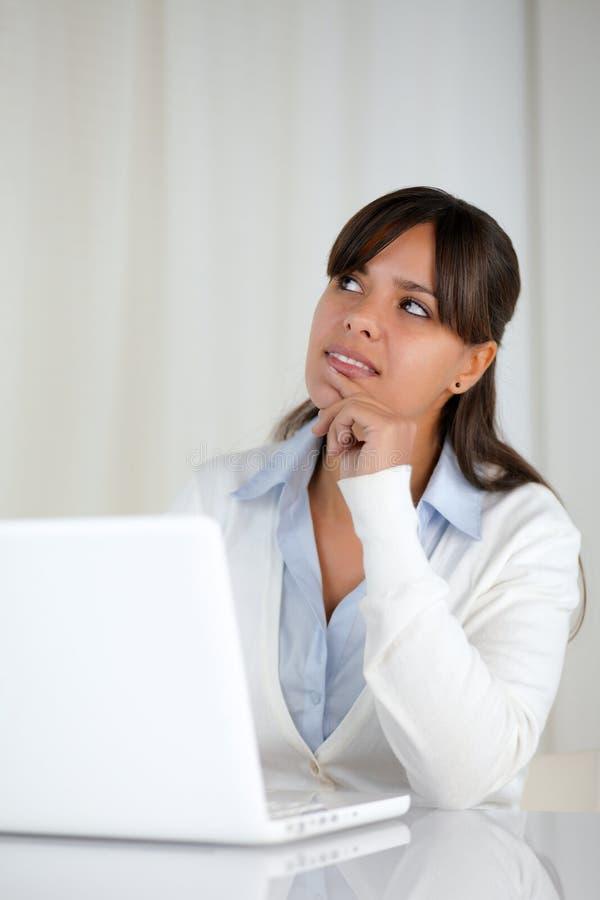 Giovane donna pensierosa che lavora al computer portatile fotografie stock