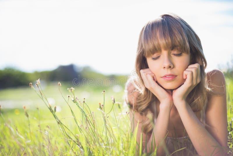 Giovane donna pensierosa che si trova sull'erba immagini stock libere da diritti