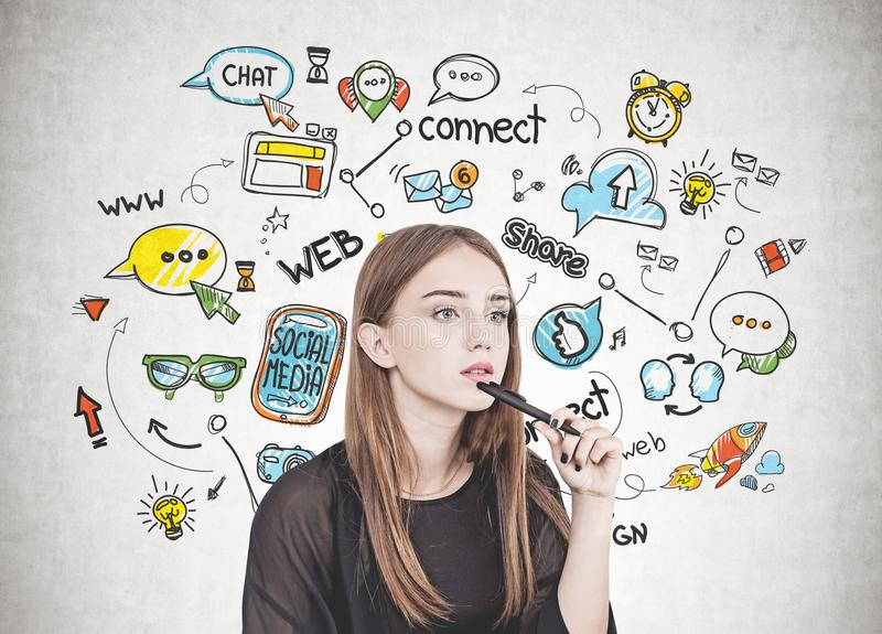 Giovane donna pensierosa con la penna, media sociali immagini stock