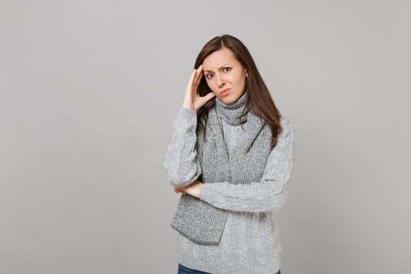 Giovane donna pensierosa interessata in maglione grigio, sciarpa che mette mano sulla testa sul fondo grigio della parete nello s immagini stock