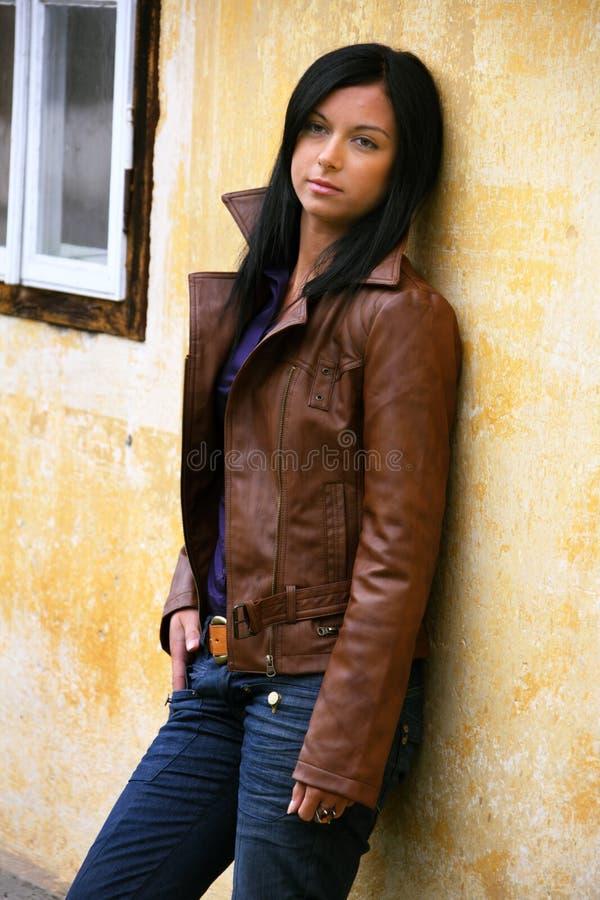 Giovane donna Pensive ad una parete della casa fotografia stock