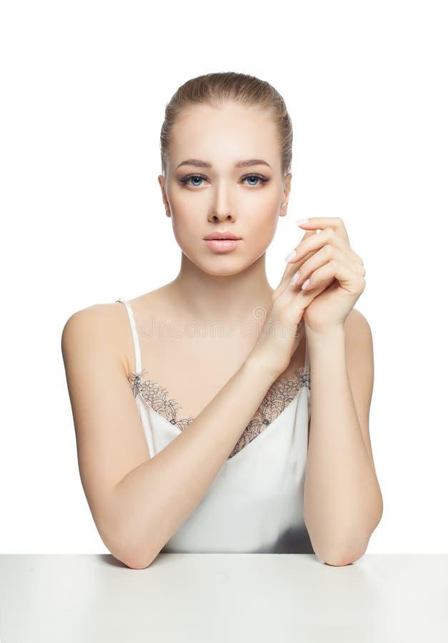 Giovane donna perfetta che si siede sulla tavola bianca Pelle sana, trucco nudo naturale e unghie del manicure francese immagini stock libere da diritti