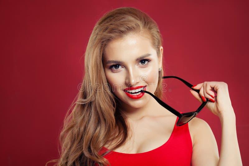 Giovane donna perfetta con gli occhiali da sole neri e trucco rosso delle labbra su fondo rosso luminoso, ritratto fotografia stock libera da diritti