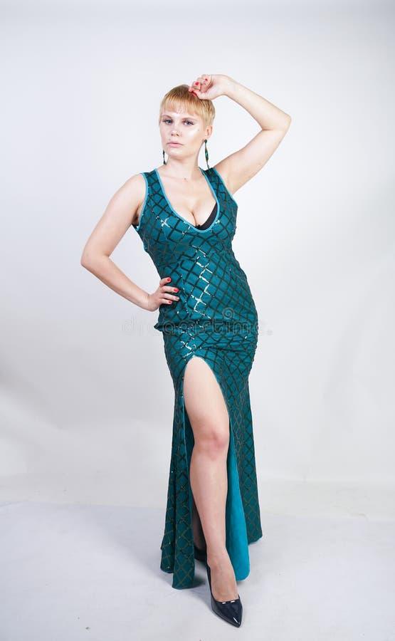 Giovane donna più affascinante di dimensione con brevi capelli biondi vestiti in un vestito lungo lussuoso da verde di sera con g fotografia stock libera da diritti