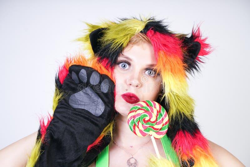 Giovane donna più incantante di dimensione in cappello di pelliccia fatto delle fibre multicolori con gli orecchi e le zampe di g immagini stock