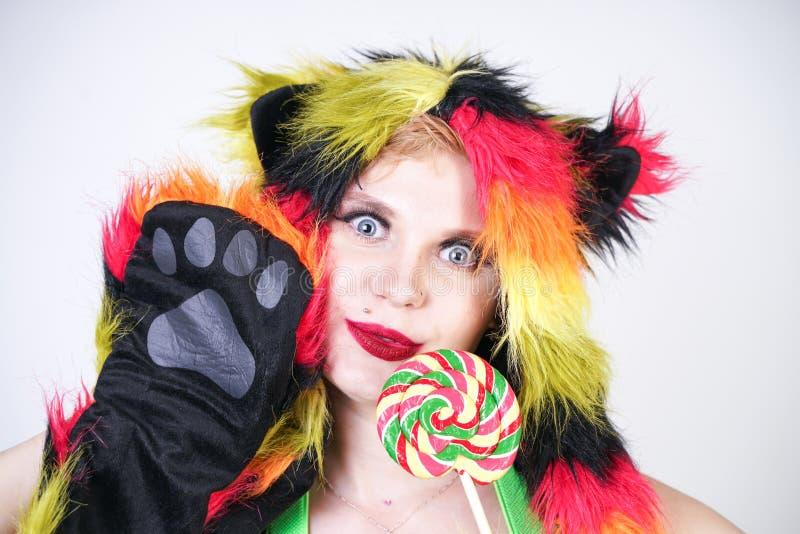 Giovane donna più incantante di dimensione in cappello di pelliccia fatto delle fibre multicolori con gli orecchi e le zampe di g fotografia stock libera da diritti
