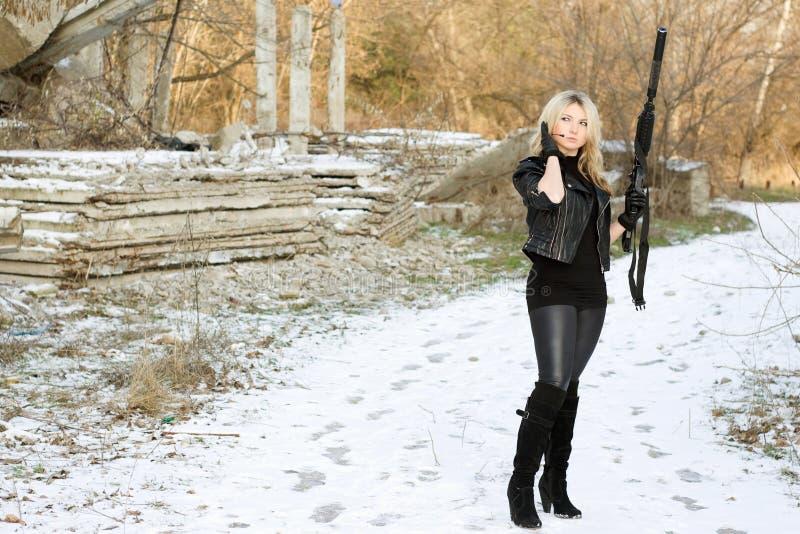 Giovane donna piacevole con una pistola fotografia stock libera da diritti