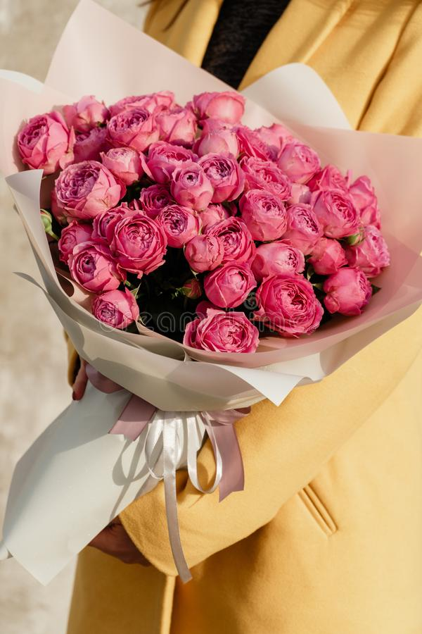 Giovane donna piacevole stessa che tiene il bello mazzo sbocciante del fiore delle rose rosa fresche in cappotto giallo, amore fotografia stock libera da diritti